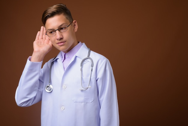 Studio shot of young handsome doctor against brown background
