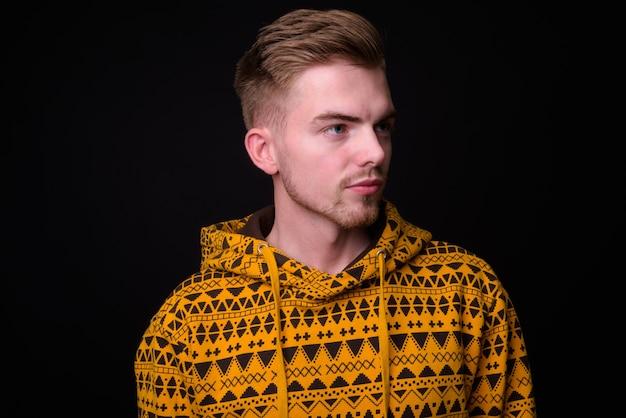 Studio shot of young handsome man against black background