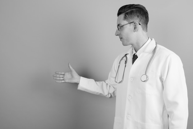 Studio shot of young handsome man doctor wearing eyeglasses against gray background in black and white