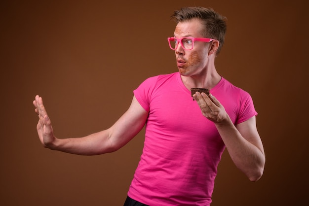 Studio shot of young handsome man wearing pink shirt with matching pink eyeglasses while having chocolate cake against brown background