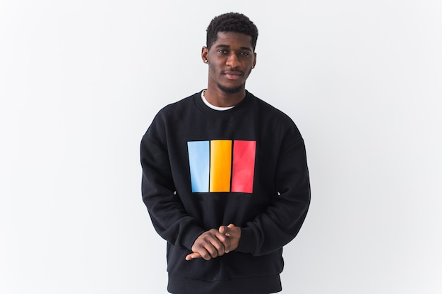Studio shot of young handsome man wearing sweatshirt against white wall