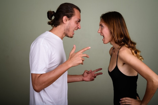 Studio shot of young handsome man and young beautiful woman together against colored background
