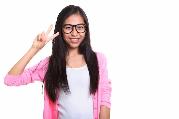 Studio shot of young happy asian teenage girl smiling
