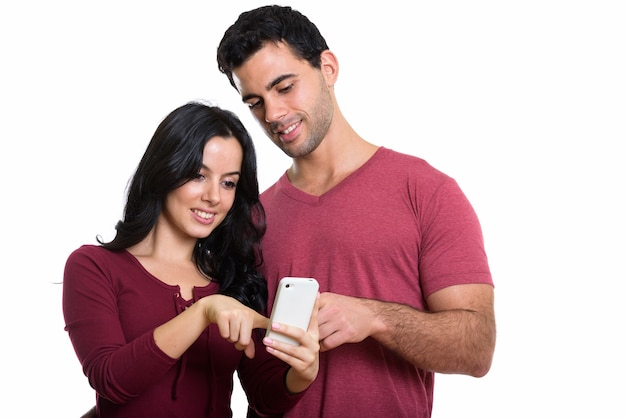 Studio shot of young happy couple smiling while using one mobile phone