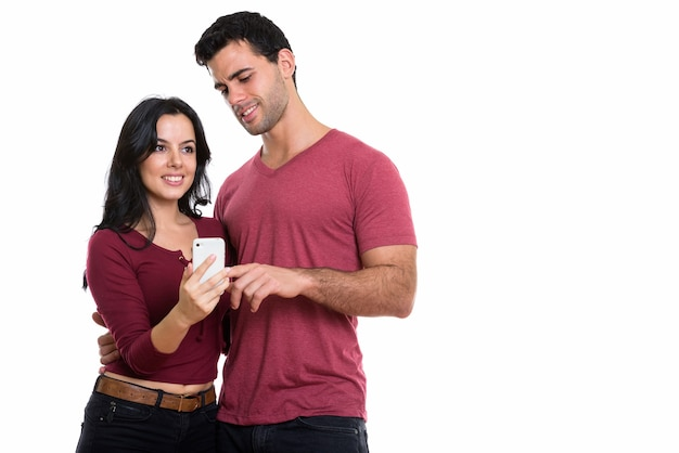 Studio shot of young happy couple smiling with man using mobile phone