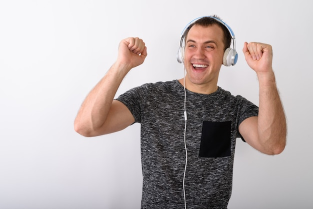 Studio shot of young happy muscular man smiling while looking ex