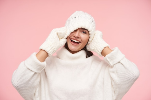 Studio shot of young joyful brown haired woman with natural makeup laughing happily while having fun and raising hands to her head, standing over pink wall