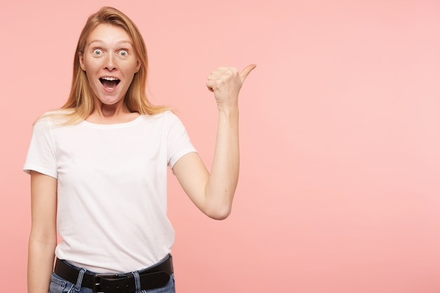 Studio shot of young joyful redhead lady with casual hairstyle pointing aside and looking amazedly at camera with wide mouth opened, isolated over pink background