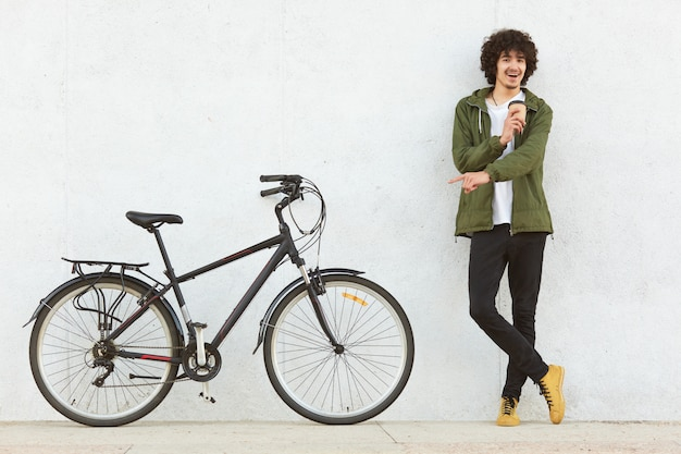 Studio shot of young male with curly hair, dressed in fashionable anorak, points with index finger at bicycle, advertises new model, drinks takeaway cooffe, makes choice, isolated on white background.
