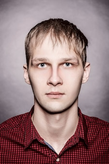 Studio shot of young man looking at the camera on light background. vertical format, he has a serious face, he is wearing a red checkered shirt.