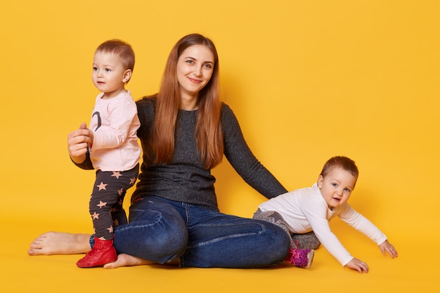 Studio shot of young mother and her twin toddlers poses in photo studio isolated over yellow. mommy sits with her infants on floor and hugs them with great love.