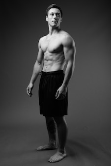 Studio shot of young muscular handsome man shirtless in black and white
