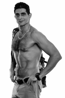 Studio shot of young muscular persian man shirtless isolated against white background in black and white