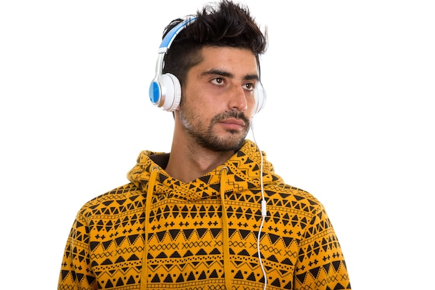 Studio shot of young persian man listening to music and thinking