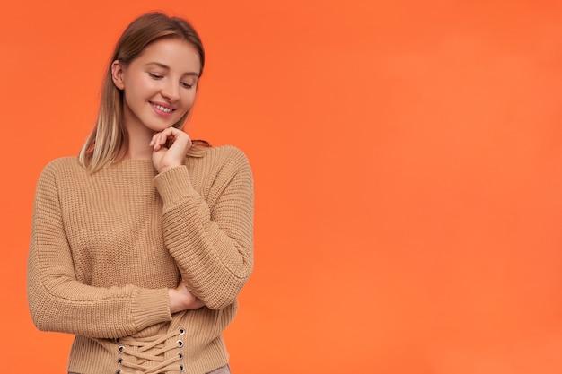 Studio shot di giovane donna bionda dai capelli corti soddisfatta che tocca delicatamente il suo viso e sorride piacevolmente mentre si sta in piedi sopra il muro arancione in abiti casual