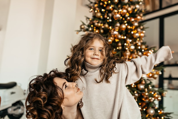 Studio shot of young pretty mother and little daughter with curly hair wearing knitted clothes posing in front of christmas tree