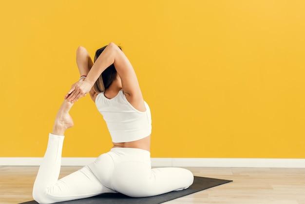 Studio shot. young sporty attractive woman practicing yoga, eka pada rajakapotasana pose