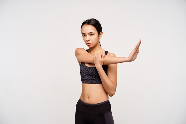 Studio shot of young sporty dark haired woman in sporty clothes stretching her arms and looking seriously at front, isolated over white wall in athletic wear