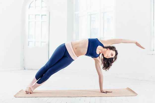 Studio shot of a young woman doing yoga exercises on white