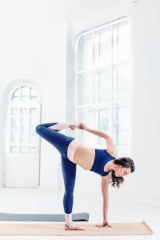 Studio shot di una giovane donna facendo esercizi di yoga su bianco