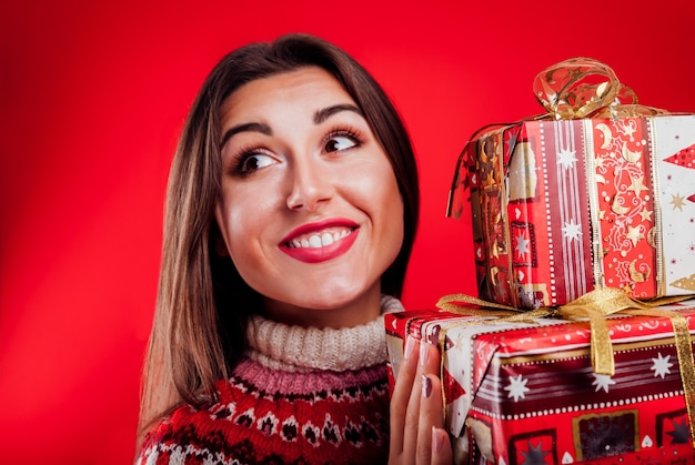 Studio shot of a young woman in icelandic sweater holding gift boxes christmas or new year gifts