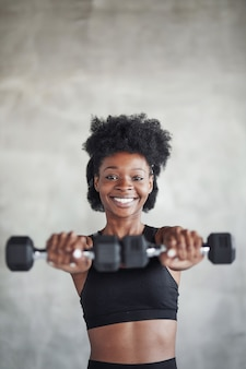 Studio shot of young woman that stands in front of grey background with dumbbells in hands