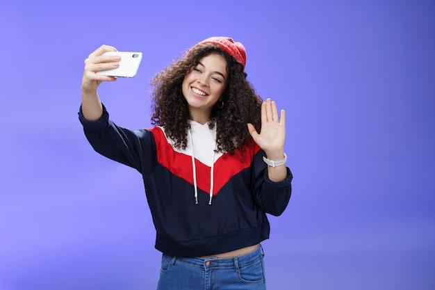 겨울 빨간 모자에 곱슬머리를 하고 웃고 지옥을 흔드는 세련된 귀여운 여성 블로거의 스튜디오 shto...