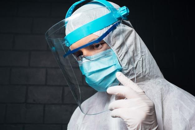 コロナウイルスとcovid-19に対してppeスーツを着ている若い医者の男のスタジオ側の肖像画。黒レンガの壁の壁。