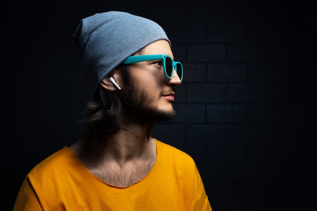 Studio side portrait of young confident man with wireless earphones wearing yellow t-shirt, blue sunglasses and grey hat on black background.