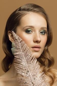 Студийное вертикальное фото молодой девушки с идеальной кожей, красивой девушки с модными серьгами и золотым пером