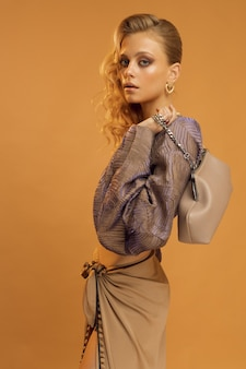 スタジオの縦の写真、ファッショナブルな服を着た女性モデル、スタイリッシュなバッグを手に、ベージュの無地の背景。高品質の写真