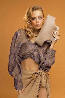 스튜디오 세로 사진, 유행의 옷을 입은 여성 모델과 그녀의 손에 세련된 가방, 베이지 색 단색 배경. 고품질 사진