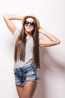 歯を見せる笑顔で陽気な女性のスタジオビュー、流行のサングラス、麦わら帽子、夏のドレスを着て、白い壁に隔離