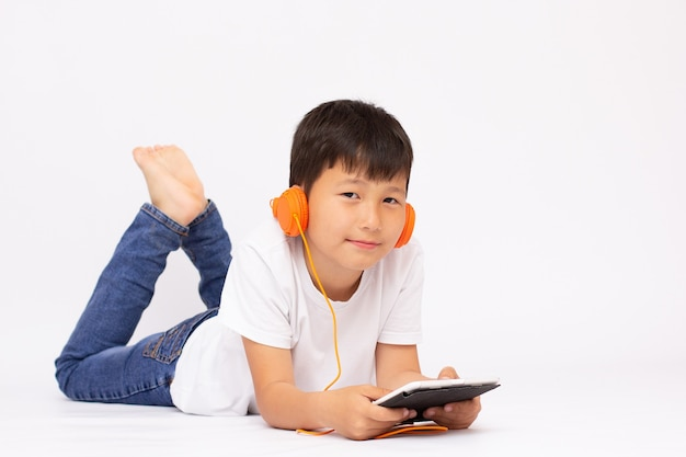 A studio view of a young preschool boy, laying on the floor and listening to music or a video on a tablet