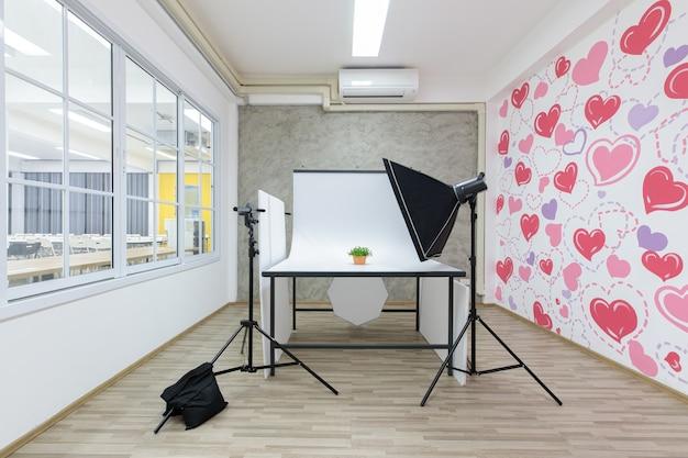 Стол и перегородка для студийной фотосессии с профессиональным фотографическим оборудованием.