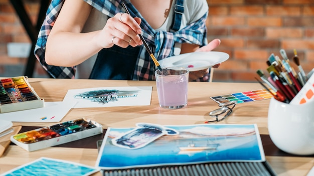 スタジオワークプレイス。仕事中のアーティスト。水彩画をやっている画家。スケッチブックとパレット用品が周りにあります。