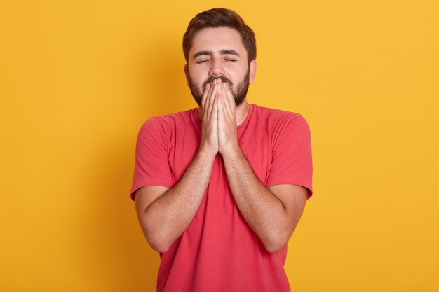 Studio young handsome guy with closed eyes hopes for fortune and good luck, stands wearing red casual t shirt, keeps hands in praying gesture, isolated on yellow.
