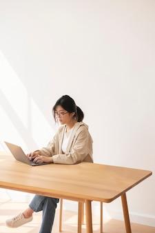 Donna asiatica studiosa che lavora a casa usando un laptop