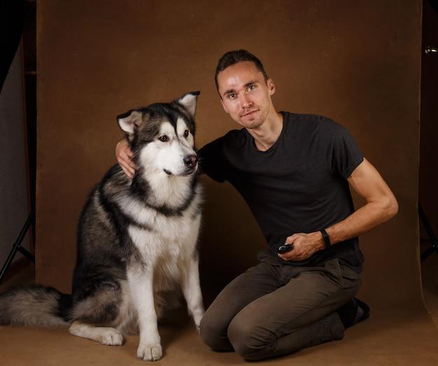 茶色の黒い地面に座っている男性とアラスカンマラミュート犬のスタッドショット