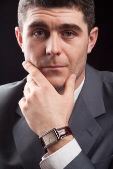 スーツを着て考えるビジネスマンのstuduoショットとカメラに探している高価な時計とネクタイ