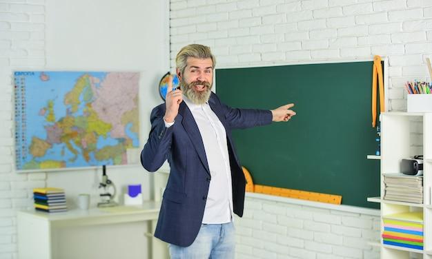 研究と教育。達成された学習成果を確認します。教師学校のレッスン。現代の学校。知識の日。学校に戻る。教室の黒板で感情的なひげを生やした男。興味を持って教える。