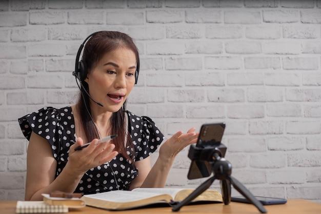 Изучите библейскую концепцию. азиатская женщина преподает и читает библию с помощью смартфона.