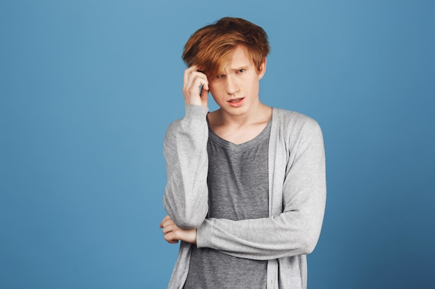 Study concept. close up portrait of concentrated young attractive ginger student in gray clothes holding hair with hand, tying to answer teacher's question, being unsure and stressed.
