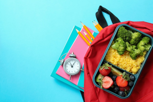 Study concept with lunch box on blue background