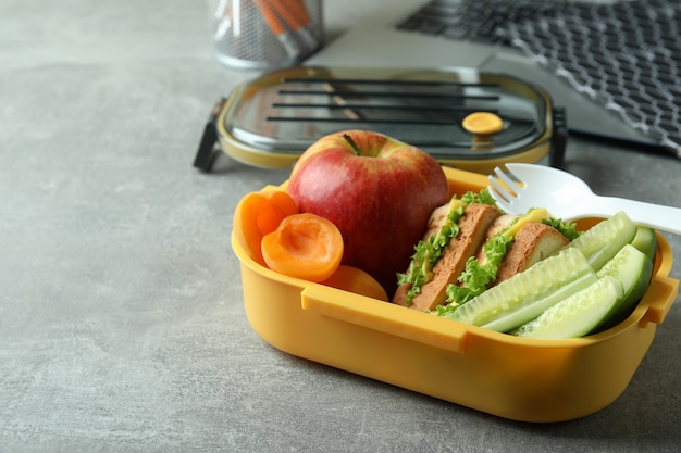 Study concept with lunch box on gray textured table
