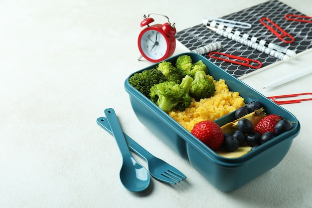 Study concept with lunch box on white textured table