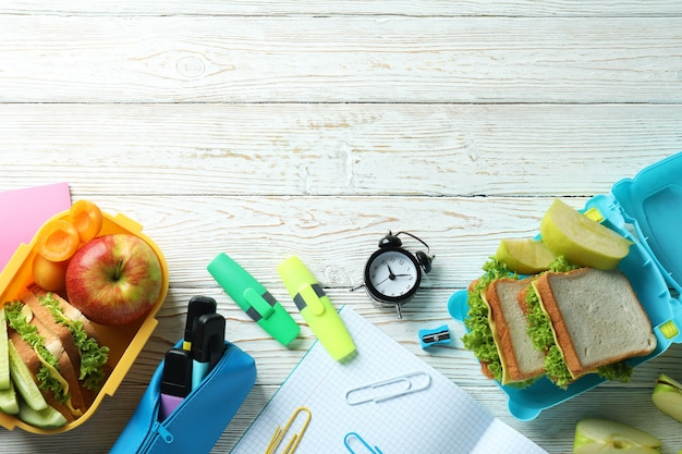 Study concept with lunch boxes on white wooden table