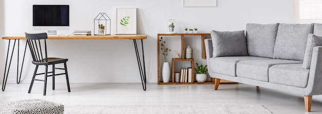 Study corner with black chair and hairpin table with empty monitor, simple poster and cactus in white living room interior with grey sofa and fresh plants
