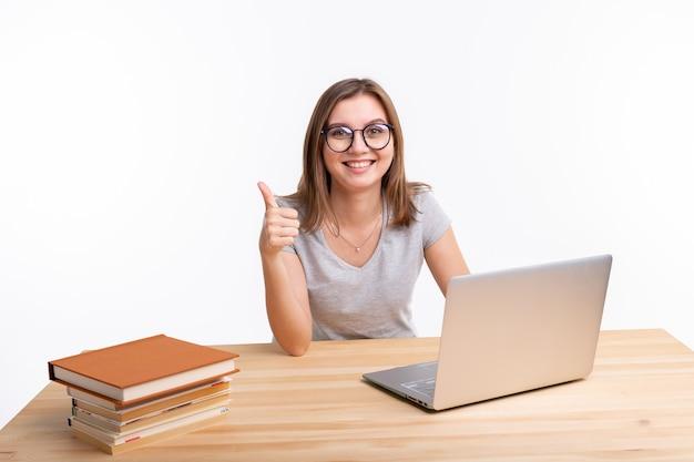 研究、教育および人々の概念。若い女性のオタクはラップトップを使用して演習を学んでいます