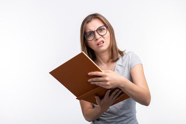 연구, 교육, 사람들 개념입니다. 여학생은 수업을 배우는 데 지쳤고, 회색 셔츠를 입고 책을 펼친 채 서 있습니다.